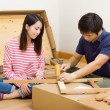 Stock Photo: Asicouple assembling new furniture