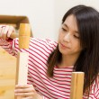 Asian woman using hammer for assembling — Stock Photo