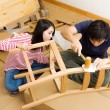 Stock Photo: Asicouple assembling new chair