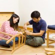Stock Photo: Asicouple assembling chair