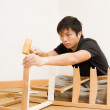 Asian man assembling chair by hammer — Stock Photo #36614837