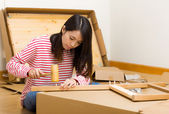 Asian woman using hammer for furniture assembling — Stock Photo