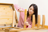 Asian woman using hammer for assembling chair — Stock Photo