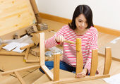 Asian woman assembling chair by hammer — Stock Photo