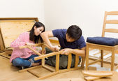 Asian couple assembling new chair — Стоковое фото