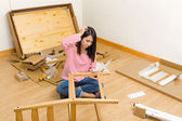 Asian woman assembling new chair with instruction — Stok fotoğraf