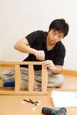 Asiatiska man montering stol hemma — Stockfoto