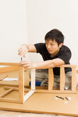 Asian man assembling chair at home — Stock Photo