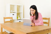 Asian woman using tablet computer at home — Stockfoto