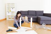 Asian woman assembling new furniture — Stock Photo
