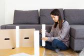 Asian woman assembling new furniture — Стоковое фото