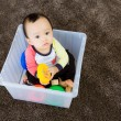 Asian baby boy playing inside the plastic box — Stock Photo