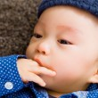Asian baby boy with finger in mouth — Stock Photo