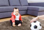 Asian baby looking at football — Stockfoto