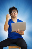 Crazy happy guy with computer laptop on blue background — Zdjęcie stockowe