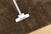 Brown carpet with vacuum cleaner — Stock Photo