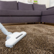 Carpet with vacuum cleaner in living room — Stock Photo #38835711