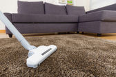 Carpet with vacuum cleaner in living room — Stock Photo