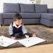 Little boy drawing picture and seating on carpet — Stock Photo