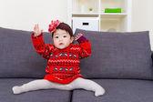 Baby girl doing legs splits on sofa — Stock Photo