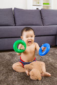 Baby playing on carpet in living room — Stock Photo