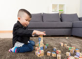Little boy playing toy block at home — Stock Photo