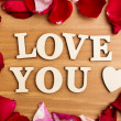 Wooden letters forming phrase Love You with rose petal besides — Stock Photo