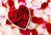 Beautiful Red rose inside the heart shape bowl with petal beside — Stock Photo
