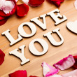Love You wooden letters with rose petal besides — Stock Photo #39374135
