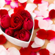 Beautiful Red rose inside heart shape bowl with petal beside — Stock Photo #39375981