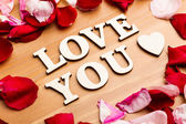 Love You wooden letters with rose petal besides — Stock Photo