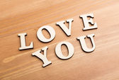 Wooden texture letters forming with phrase Love You — Stock Photo