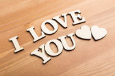 Wooden texture letters forming with phrase I Love You — Stock Photo