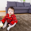 Baby girl sitting on carpet with water bottom and doll — Stock Photo #39423849