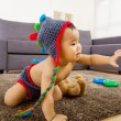 Baby crawling on carpet and one hand up — Stock Photo