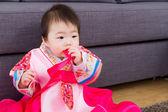 Korean baby girl bite ribbon at home — Stock Photo