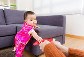 Chinese baby taking red pocket from adult — Stock Photo