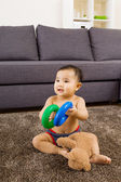 Baby seating on carpet and play doll — Stock Photo
