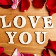 Love you wooden text and rose petal — Stock Photo