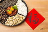 Chinese new year snack tray and chinese calligraphy — Stock Photo