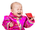 Chinese baby crying with red pocket — Stock Photo