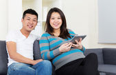 Pregnant mother and father using digital tablet at home — Stock Photo