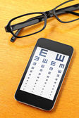 Eyechart on mobile with glasses — Stok fotoğraf
