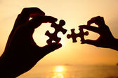 Man and woman hands trying to connect puzzle pieces — Stock Photo