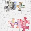 Stock Photo: US dollar and chinese yuwith white puzzle