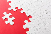 Incomplete puzzle with missing piece over red background — Stock Photo