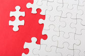 Incompleted white puzzle on red background — Stock Photo