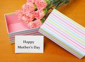Gift and carnation to mum — Stock Photo