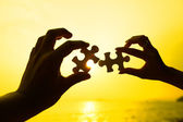 Two hands trying to connect puzzle pieces with sunset background — Stock Photo