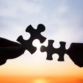 Two hands trying to connect puzzle pieces  — Stock Photo